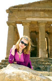 Blond girl in agrigento. Girls with sunglass leanding against a temple greek column in agrigento sicily royalty free stock photo