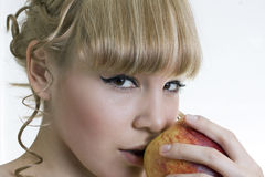 Blond girl with apple Royalty Free Stock Photos