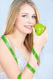 Blond girl with apple and measuring tape Royalty Free Stock Images