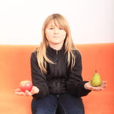 Blond girl with apple and pear Stock Images