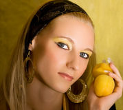Blond girl with apricot Stock Photos