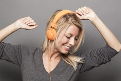 Blond girl arms up with earphones with eyes closed Stock Photography