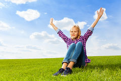 Blond girl with arms up sitting on green grass Royalty Free Stock Images