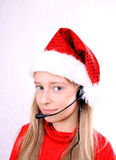 Blond girl as Mrs. Santa with headset Royalty Free Stock Images