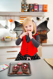 Blond girl in bat costume eating Halloween biscuits in kitchen Royalty Free Stock Images