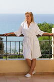 Blond girl in bathrobe on hotel balcony Royalty Free Stock Photos