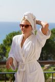 Blond girl in bathrobe on hotel balcony Stock Photo