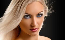 Blond Girl. Beautiful Sexy Blond Girl. Long Hair. Blonde on Black Background. Holiday Makeup Royalty Free Stock Photo
