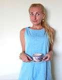 A blond girl in bewilderment or perplexity. A woman in disgust, young fair haired girl wearing a blue dress looking aside at her husband, bou-friend, neighbour Royalty Free Stock Photography