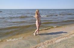 Blond girl in a bikini on the beach. Beautiful young woman in a colorful bikini on sea background Stock Image