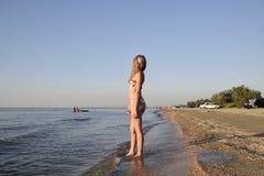 Blond girl in a bikini on the beach. Beautiful young woman in a colorful bikini on sea background Royalty Free Stock Image