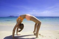 Blond girl in bikini doing yoga at the beach Stock Photography