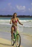 Blond girl in bikini riding her bike Stock Photo