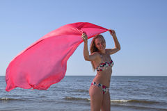 Blond girl in a bikini standing on the beach and holding a red silk handkerchief. Beautiful young woman in a colorful bikini on se. A background Royalty Free Stock Photos