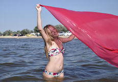 Blond girl in a bikini standing on the beach and holding a red silk handkerchief. Beautiful young woman in a colorful bikini on se. A background Royalty Free Stock Photo