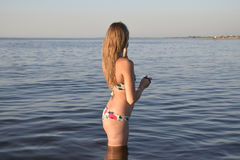 Blond girl in a bikini standing in the sea water. Beautiful young woman in a colorful bikini on sea background Stock Images