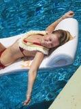 Blond girl in bikini at a swimming pool Stock Photos