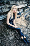 Blond girl in a black leather suit Stock Images