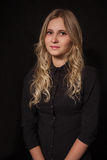 Blond girl in black. Pretty blond girl in black blouse at dark Royalty Free Stock Photography