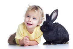 Blond girl and black rabbit. Little girl with a rabbit lying on a white background Royalty Free Stock Photography