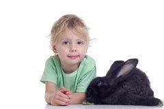 Blond girl and black rabbit. Little girl with a rabbit lying on a white background Stock Images