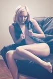Blond girl on black sofa Stock Photography