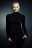 Blond girl in black sweater Stock Images