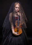 Blond girl with black veil holding violin. On black background Royalty Free Stock Image