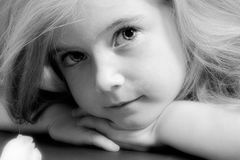 Blond girl in black and white. Cute blond girl with strong eye-contact, lying on her hands Stock Photography