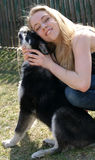 Blond girl with black-white dog Royalty Free Stock Photography