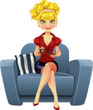 Blond girl in blue armchair with cup of coffee Royalty Free Stock Images