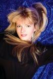 Blond girl on blue background Stock Image
