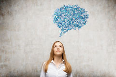 Blond girl with blue dialogue box. Blond girl is standing against concrete wall with blue thought bubble above her head. Concept of virtual life and social media Stock Images