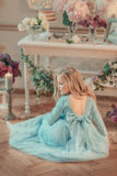 Blond girl in blue dress and with a flower on the head. The flower Studio is sitting on the floor blonde girl in blue long dress and with a flower on the head Royalty Free Stock Photography