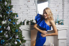 Blond girl in blue dress poses near christmas tree Stock Image