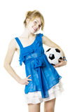 Blond girl in a blue dress with soccer ball Stock Photo