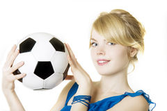 Blond girl in a blue dress with soccer ball Royalty Free Stock Image