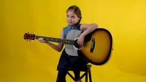 Blond girl blue eyes plays guitar stock footage