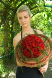 Blond girl with a bouquet. Of red roses Royalty Free Stock Photo