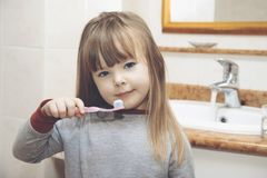Blond girl with braces smiling while brushing your teeth. Close up royalty free stock photo