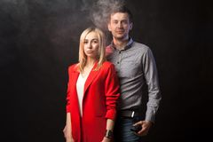 Blond girl in brightly red suit with jacket and white blouse and tall dark-haired guy royalty free stock photography