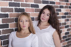 Blond girl and brunette in white shirts standing with serious faces. Two beautiful young good looking girls blond and brunette wearing white shirts standing near stock images