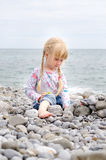 Blond Girl Building Stone Wall on Rocky Beach Royalty Free Stock Photography