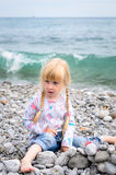Blond Girl Building Stone Wall on Rocky Beach Royalty Free Stock Images