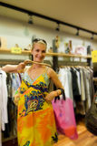 Blond girl buying clothes in a. Shop Royalty Free Stock Image