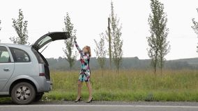 Blond girl calling cellphone in a panic near her broken car with open trunk on a country road stock video
