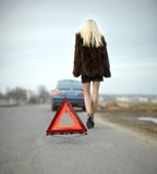 Blond girl calling for help broken car triangle Royalty Free Stock Photos