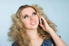 Blond girl is calling with a mobile phone. Royalty Free Stock Photo