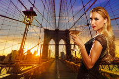 Blond girl cheers with vermout cup in NYC sunset Stock Image