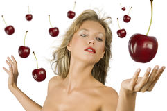 Blond girl with cherry stock photography
